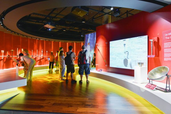 "The Olympic Museum Lausanne, 2015 - Interior view. Permanent exhibition at the Level +1. Some visitors in the area ""The flame"". On the right, the parabola."