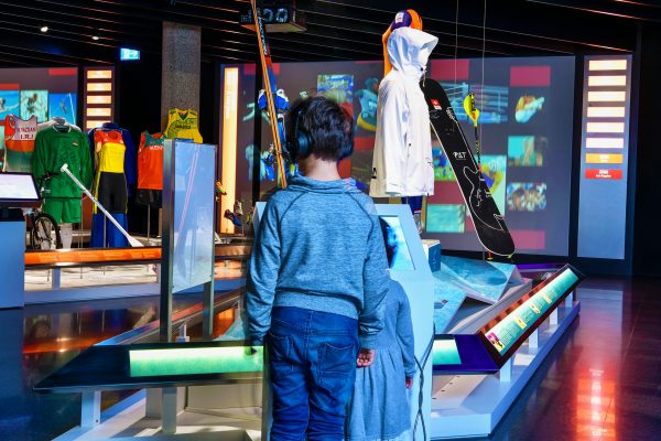 "The Olympic Museum Lausanne, 2018 - Interior view. Permanent exhibition. Children in the area ""The Olympic Games"", at the Level 0: the sports equipments of the Winter OG."